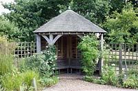 An oak timber garden arbour with oak benches and oak tiled roof.
