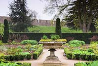 The East Garden, a formal space with low Euonymus hedging, roses and herbaceous planting at Bishop's Palace Garden, Wells, Somerset, UK.