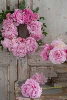 Pink Peony wreath on vintage French door, with urn arrangement of cut peony blooms.