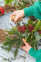 Woman securing conifer to woven wreath form with string