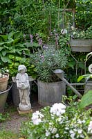 Sculpture of a boy, between containers of plants