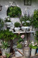 View of old facade with sewing table, mirror, plants in pots and metal pots