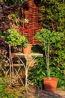 Ornate metal table and chair in the cottage garden at the front of the barn. A terracotta pot of pelargoniums sits on the table.