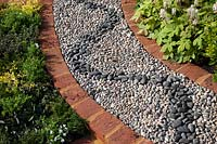 Brick -sinuous path made from pebbles