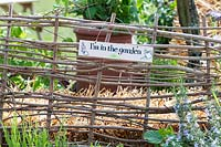 'Im in the garden' sign on a rustic fence