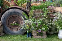 Wildflowers on 'Sophie's country Garden Flowers' display with woven fence panel and tractor