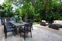 Modern, black table and chairs on raised paved patio, in tropical garden with lush planting. Florida, USA. Garden design by Craig Reynolds Landscape Architecture.