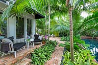 View of patio and terrace with table and chairs surrounded by Solitaire palms. Key West Classic Garden, designed by Craig Reynolds. Key West, Florida, USA.