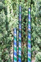 Blades - panels of glass and steel-- displayed amongst conifer foliage