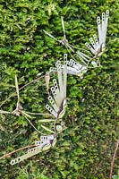 Birds and Bees - artwork made of steel cutlery - shown against a hedge