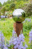 Close up of reflection in stainless steel mirror globe mounted on wooden post in meadow of