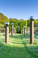 View along grass path with an avenue of stainless steel mirror globes mounted on wooden posts