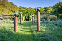 View along grass path with avenue of stainless steel mirror globes mounted on