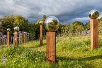 Avenue of stainless steel mirror globes mounted on wooden posts, 