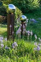 Reflections in stainless steel mirror globes mounted on wooden posts, in meadow with 