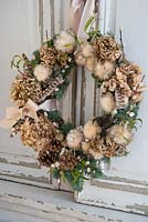 Natural wreath with Hydrangeas, fir and feathers, hanging from cupboard doors