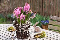 Easter decoration on garden table, with flowering Hyacinthus, Salix branches and quail eggs.