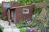 The Watchmakers' Garden at BBC Gardeners World Live 2019 - A view of watchmakers cottage surrounded by cottage planting
