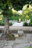 Formal garden with seating, central millstone water feature and topiary