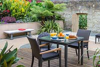 Intimate dining area on a deck overlooking a courtyard, edged in beds of Australian tree ferns, cannas, verbenas and sedums.