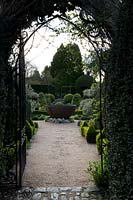 View through gothic metal gateway to central metal water feature and Knot garden beyond, at Abbey House Gardens, Malmesbury, UK.