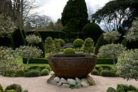 View across Knot garden with topiary forms and central metal water feature at Abbey House Gardens, Malmesbury, UK.