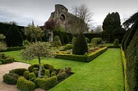 View across knot garden and topiary forms at  Abbey House Gardens, Malmesbury, UK.