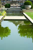 View up modern water feature with paved area.