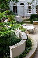 View of paved, urban garden, with dining area and formal planting.