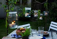 Jam jar lanterns with candles suspended from wire hanging over garden table.