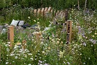 A line of bug hotels surrounded by flowering perennials in BBC Springwatch garden, RHS Feature Garden, RHS Hampton Court Palace Garden Festival, 2019.