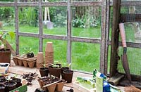 Potting bench with seedlings with view to garden through window
