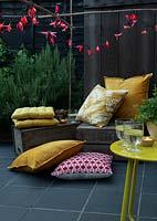 Fairylights decorated with colourful paper shapes create beautiful decorative outdoor lighting, used here over bamboo cane supports in a seating area with fruit crates and cushions.