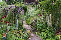 A paved pathway leading through a cut flower bed screened behind trellis and clematis