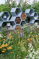 A wall made from honeycomb shapes containing twigs to encourage solitary bees, surrounded by nectar-rich flowers. The Urban Pollinator Garden, Designed by Caitlin McLaughlin. RHS Hampton Court Palace Garden Festival, 2019.