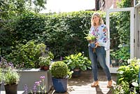 Sarah Jarman - garden owner on deck holding a Verbena in pot