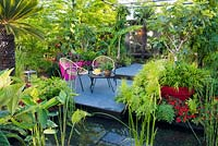Seating area in the garden with tender planting in pots by the pond with aquatic plants Equisetum hyemale, Cyperus and Thalia. B and Q Bursting Busy Lizzie Garden at RHS Hampton Court Palace Garden Festival Show 2018
