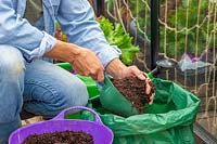 Woman adding compost to the grow bag using a scoop