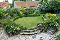Bird's-eye view of walled rose garden, with curving lawn and steps in shape of figure-of-eight.
