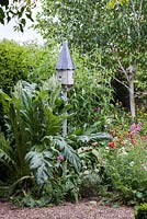 A dovecote style nesting box creates a pretty focal point in the gravel garden.