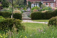 View over wildflowers to lawn enclosed in yew hedges, and path leading up steps to main terrace.