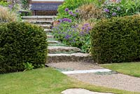 Stone steps, interspersed with woolly thyme, and edged in Geranium x magnificum 'Rosemoor' and Allium 'Purple Sensation',