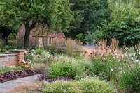 View over border of gaura, hardy geranium, clumps of feather reed grass, Calamagrostis x acutiflora 'Karl Foerster', coneflowers and achilleas, towards brick summerhouse.