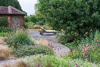 A stone terrace with loungers is reached via a straight path edged in hardy geraniums, penstemons, coneflowers and a clump of Pennisetum macrourum, African feather grass.