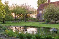 Sunset is mirrored in a wildlife pond. Beyond, the 1937 house is bedecked in wisteria. In the lawn, old apple trees break out in blossom above tulips and daffodils.