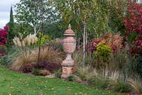 A terracotta urn stands amidst ornamental grasses, Asters, Pampas grass, Maples and silver birches.