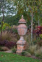 An urn raised high above a bed of birches and ornamental grasses.