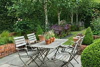 A small paved courtyard with dining table and chairs, is hidden away behind a tall hornbeam hedge and silver birches, Betula utilis var. jacquemontii.