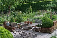 A small paved courtyard with dining table and chairs, flanked by domes of box, overlooks a box parterre planted with Bistort, hardy Geraniums, Centaurea, Foxgloves, ragged robin, Astrantias, Aquilegias and Roses.