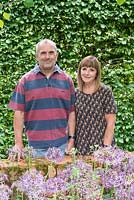 Garry and Alison Szafranski in their front garden. Behind a hornbeam hedge, in front a bed of Allium cristophii.
